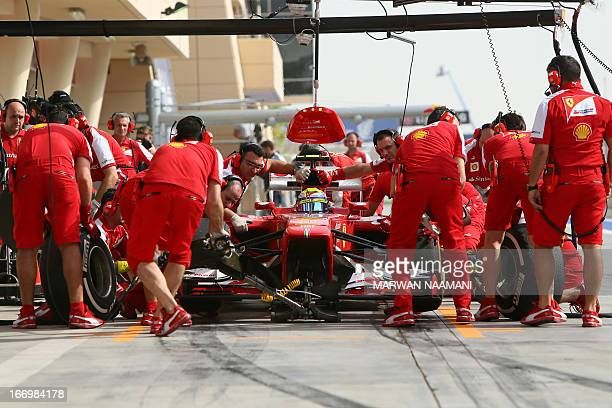 Mechanics change tires on the car of Ferrari's Brazilian driver Felipe Massa in the pits on April 19 2013 during the second practice session at the...