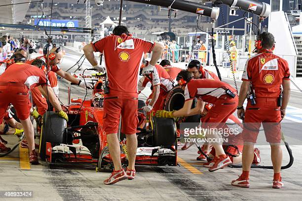 Mechanics change tires on the car of Ferrari's Finnish driver Kimi Raikkonen in the pits during the second practice session at the Yas Marina circuit...