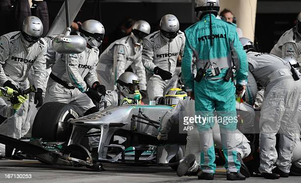 Mechanics change tires on the car of Mercedes' German driver Nico Rosberg in the pits at the Bahrain International Circuit in Manama on April 21 2013...