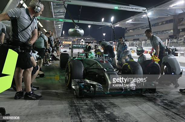 Mechanics change tires on the car of MercedesAMG's British driver Lewis Hamilton in the pits during the second practice session at the Yas Marina...