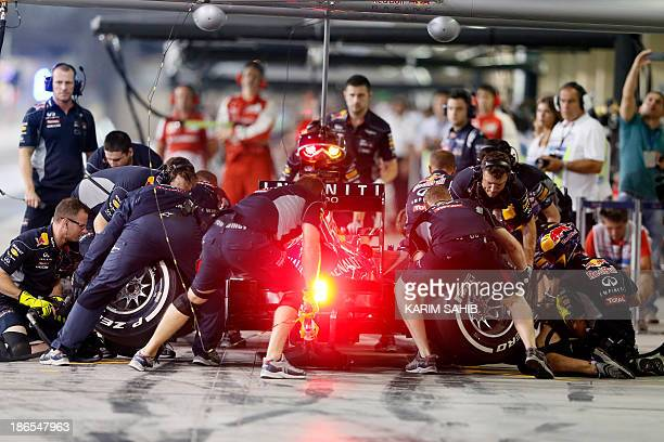 Mechanics change tires on the car of Red Bull Racing's German driver Sebastian Vettel in the pits during the second practice session at the Yas...