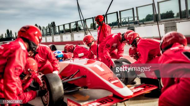 mechanics changing tires on a formula during a pit stop - sports race stock pictures, royalty-free photos & images