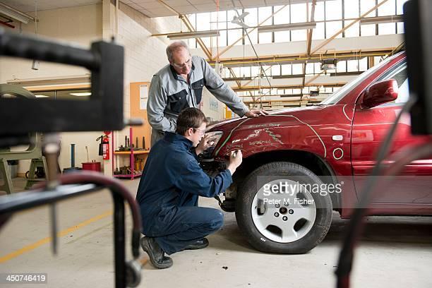 Mechanics checking damaged automobile