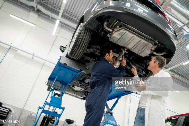 Mechanics fixing a car at an auto repair shop