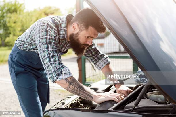 mechanics fixing a car in a garage - auto repair shop exterior stock pictures, royalty-free photos & images