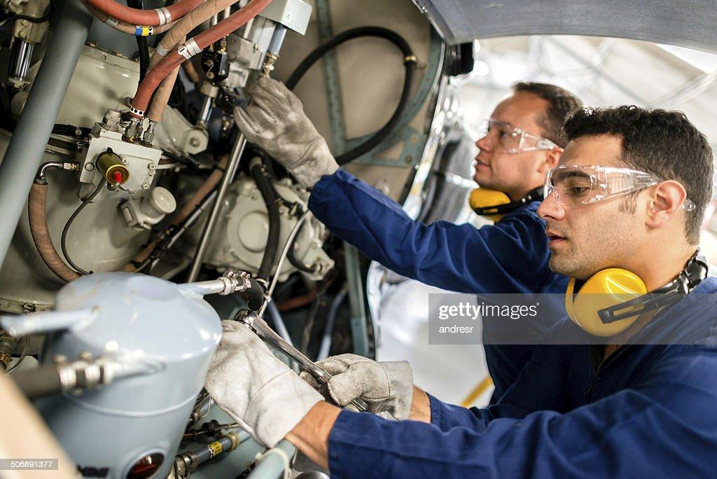 Mechanics fixing a helicopter : Stockfoto