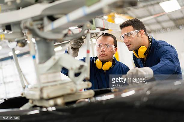 mechanics fixing a helicopter - aircraft stock photos and pictures