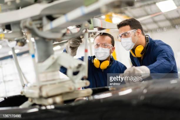werktuigkundigen die een helikopter bevestigen terwijl het dragen van een facemasks - luchtvaartuig stockfoto's en -beelden