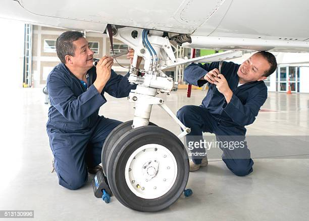 Mechanics fixing an airplane