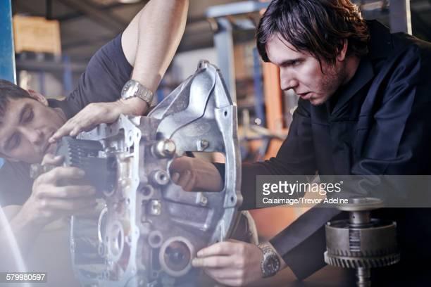 Mechanics fixing part in auto repair shop