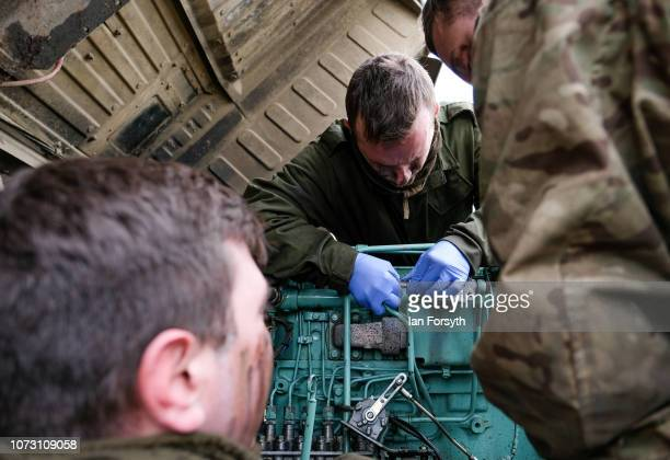 Mechanics from the Royal Electrical and Mechanical Engineers work on the engine of a vehicle as troops from 4 Regiment Royal Logistic Corps deploy to...