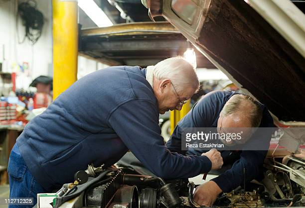 Mechanics help each other during auto repair