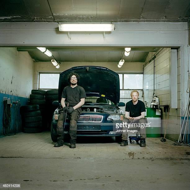 Mechanics in auto repair shop, portrait