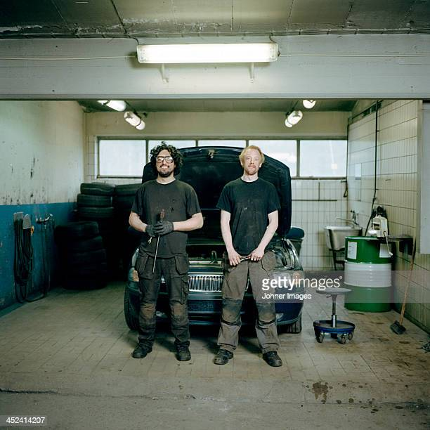 Mechanics in auto repair shop, portrait