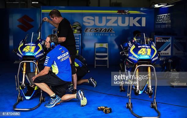 TOPSHOT Mechanics inspect the bike of Team Suzuki Ecstar's Spanish rider Aleix Espargaro during the second practice session of the 2016 Malaysian...