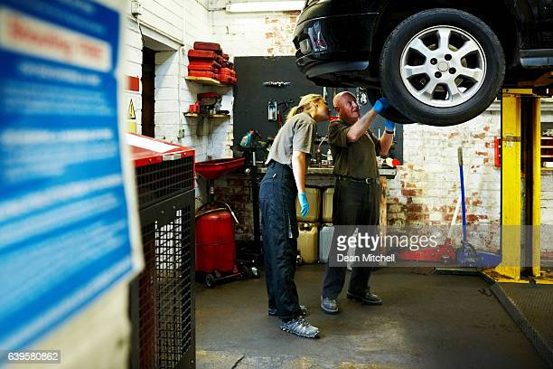 Mechanics inspecting a car in garage