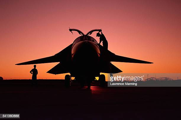 Mechanics Inspecting F-111 at Sunset