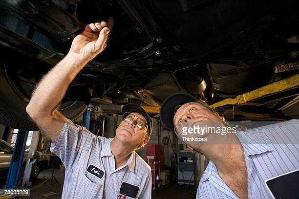 Mechanics looking up under car on lift