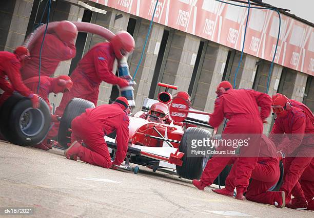 Mechanics Maintaining a Red Formula One Car at a Pit Stop