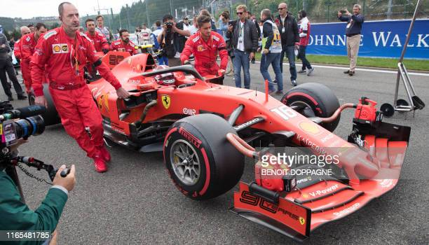 Mechanics move the car of Ferrari's Monegasque driver Charles Leclerc to the starting grid ahead of the Belgian Formula One Grand Prix at the...