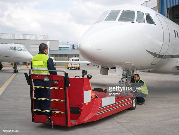 Mechanics moving an airplane