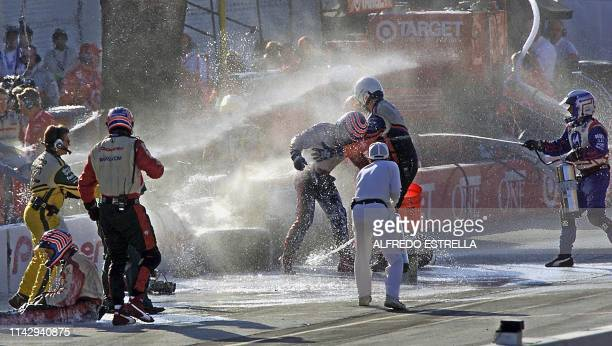 Mechanics of Brazilian driver Tony Kanaan of the MoNunn Racing team are aided by team members after suffering an accident at the pit stop during a...