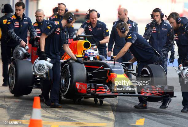Mechanics of Red Bull pushes the car of Australian Formula One driver Daniel Ricciardo of Red Bull back into the pit during the training session for...