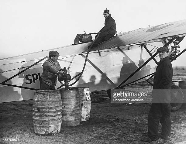 Mechanics pumping 500 gallons of fuel into the Fokker monoplane 'Splitdorf' which Bert Acosta and Emile Burgin will pilot in an attempt to recapture...