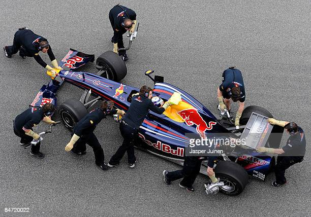 Mechanics push Sebastian Vettel of Germany and Red Bull Racing F1 in the new RB5 back in to the team's garage during formula one testing at the...