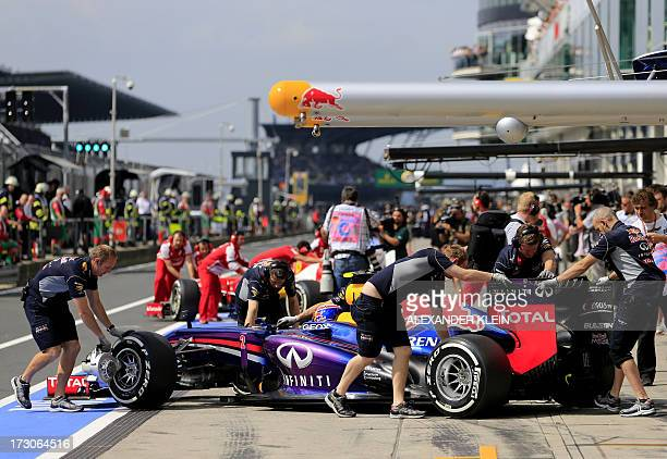 Mechanics push the car of Red Bull Racing's Australian driver Mark Webber and Ferrari's Spanish driver Fernando Alonso in the pits during the third...