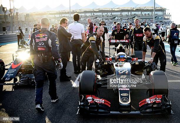 Mechanics push the cars of McLaren Honda's Spanish driver Fernando Alonso and Lotus F1 Team's French driver Romain Grosjean before the start of the...