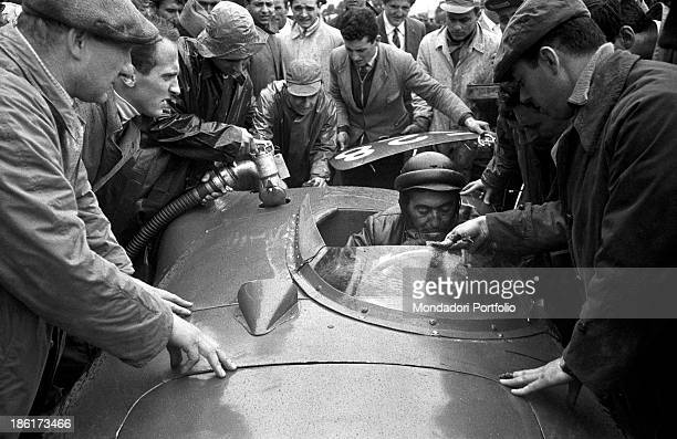 Mechanics refuelling the car of the Italian racing car driver Giuseppe Musso running the Mille Miglia Automobile Race The pilot drinking a glass of...