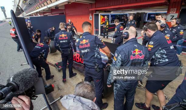 Mechanics stand around the new car of Australian Formula One pilot Daniel Ricciardo of Red Bull at the Formula One preseason testing at the Circuit...