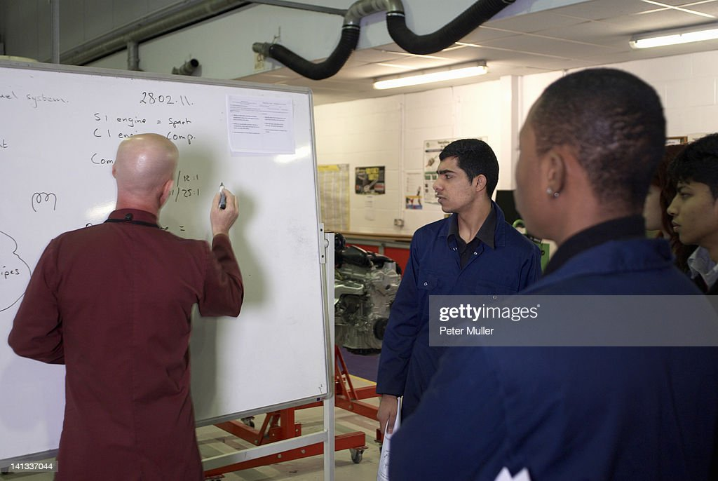 Mechanics teacher writing on board : Stock Photo