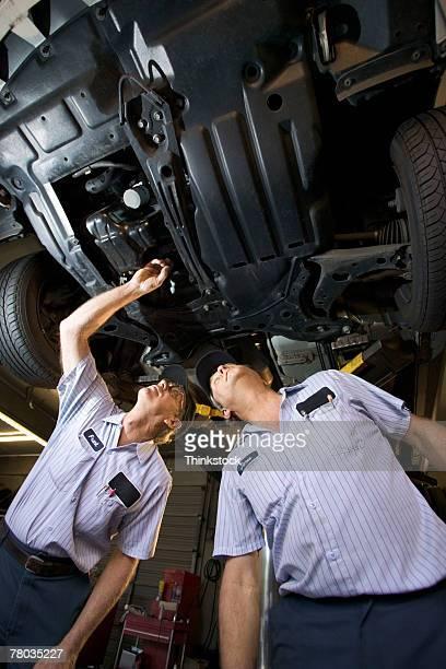 Mechanics under car on lift