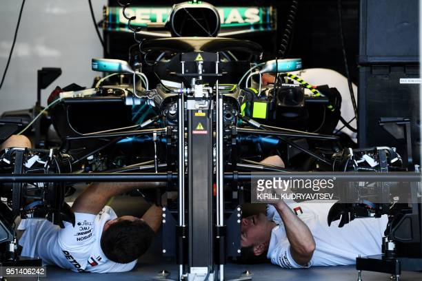 TOPSHOT Mechanics work in the garage of Mercedes Britain's driver Lewis Hamilton ahead of the Formula One Azerbaijan Grand Prix in Baku on April 26...