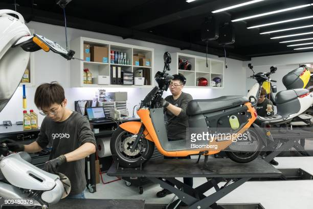 Mechanics work on Gogoro Inc scooters at one of the company's stores in Taipei Taiwan on Monday Jan 22 2018 Gogoro the Taiwanese...