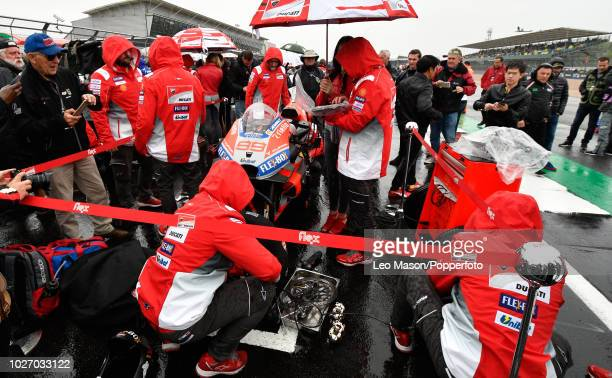 Mechanics work on the bike of Jorge Lorenzo of Spain and Ducati on the starting grid 5 minutes before the race was postponed due to persistent rain...