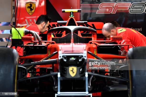 Mechanics work on the car of Ferrari's Monegasque driver Charles Leclerc ahead of the Abu Dhabi Formula One Grand Prix at the Yas Marina circuit on...