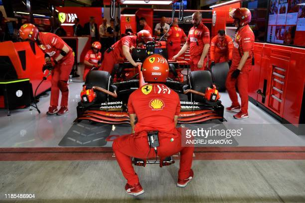 Mechanics work on the car of Ferrari's Monegasque driver Charles Leclerc after the second practice session on November 29 at the Yas Marina Circuit...
