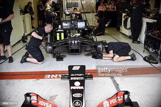 Mechanics work on the car of Lotus F1 Team's French driver Romain Grosjean in the pit during the third practice session at the Yas Marina circuit in...