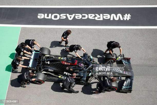 Mechanics work on the car of Mercedes' British driver Lewis Hamilton as he competes during the qualifying session at the Circuit de Catalunya in...