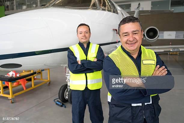 Mechanics working at an airplane hangar