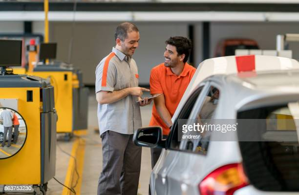 Mechanics working at an auto repair shop fixing a car