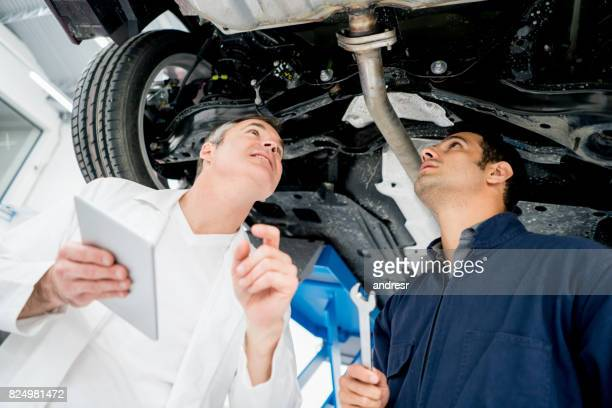 Mechanics working at an auto repair shop looking at a car's chassis