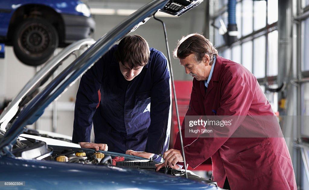 Mechanics working in garage : Stock Photo