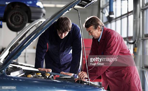 mechanics working in garage - hugh sitton stockfoto's en -beelden