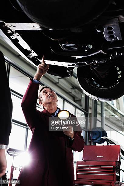 mechanics working in garage - hugh sitton stock pictures, royalty-free photos & images