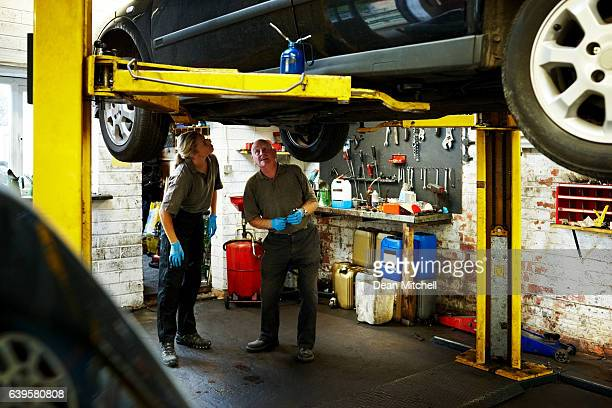 Mechanics working on a car in garage