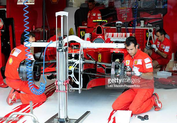 Mechanics working on a Ferrari car during practice day of the British F1 Grand Prix at the Silverstone race track in Northamptonshire England UK